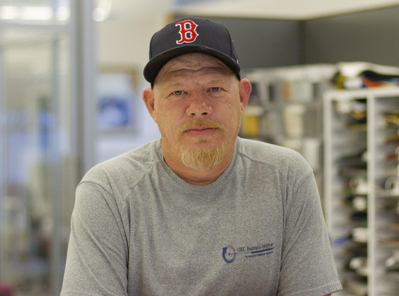 Male lead installer posing for headshot with Boston RedSox baseball cap and grey tshirt.